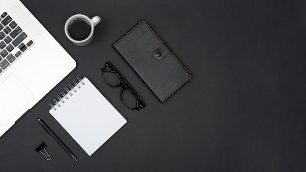Bovenaanzicht van laptop; thee; pen; spiraalvormige blocnote; bril; dagboek en paperclip op zwarte achtergrond