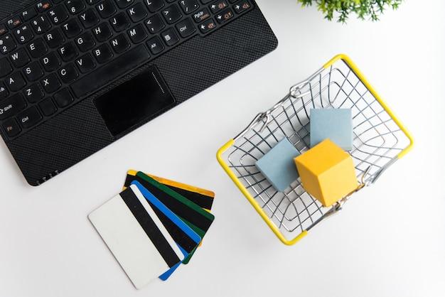 Bovenaanzicht van laptop, winkelmandje en creditcards. online winkelen en bezorgen concept
