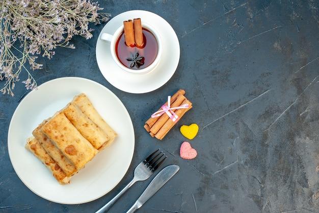 Bovenaanzicht van lavash-wraps op een bord en bestek zet een kopje zwarte thee, kaneellimoenen op zwarte achtergrond