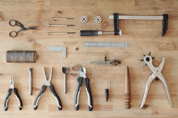 Bovenaanzicht van lederen werkgereedschapset zoals roterende pons, liniaal, draad, tang, randverbrandingsmachine op houten tafel