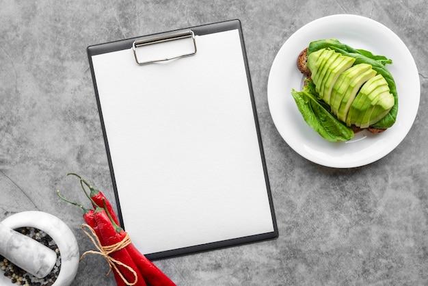 Bovenaanzicht van leeg menu met avocado en chili pepers