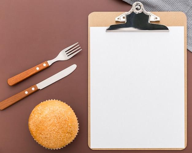 Bovenaanzicht van leeg menu met bestek en broodje