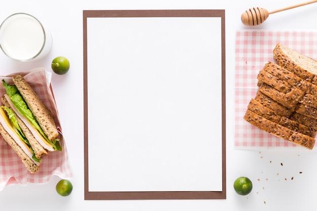 Bovenaanzicht van leeg menu met brood en sandwiches