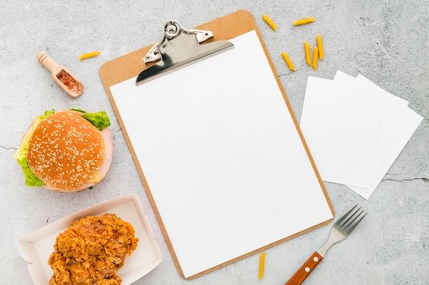 Bovenaanzicht van leeg menu met hamburger en gebakken kip
