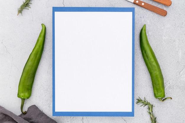 Bovenaanzicht van leeg menu met paprika en bestek