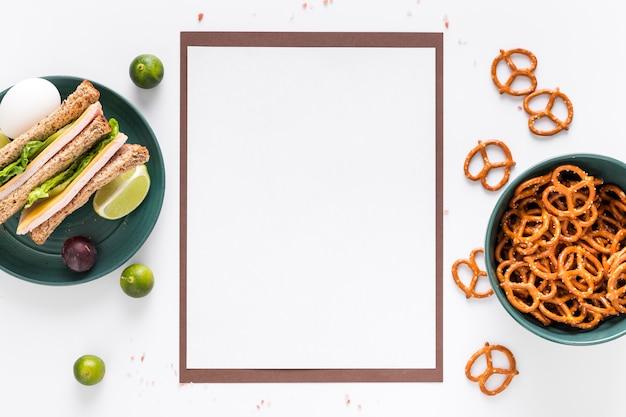 Bovenaanzicht van leeg menu met sandwiches en pretzels