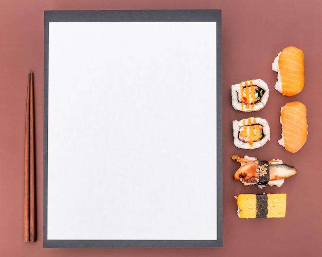 Bovenaanzicht van leeg menu met stokjes en sushi