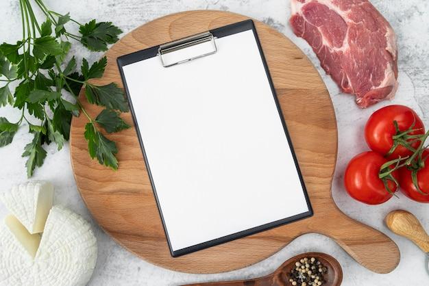 Bovenaanzicht van leeg menu met vlees en tomaten