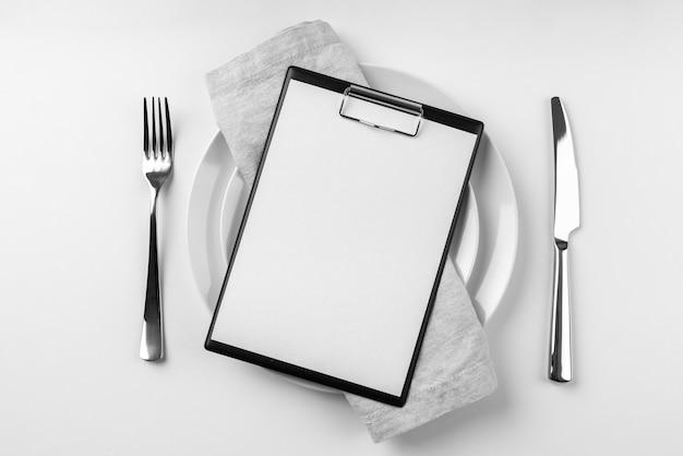 Bovenaanzicht van leeg menu op plaat met bestek