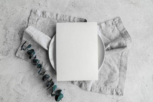 Bovenaanzicht van leeg papier op plaat met bladeren