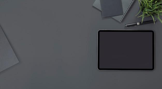 Bovenaanzicht van leeg scherm tablet en benodigdheden op zwarte achtergrond.