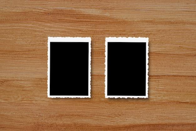 Bovenaanzicht van lege fotolijsten op houten tafel achtergrond.