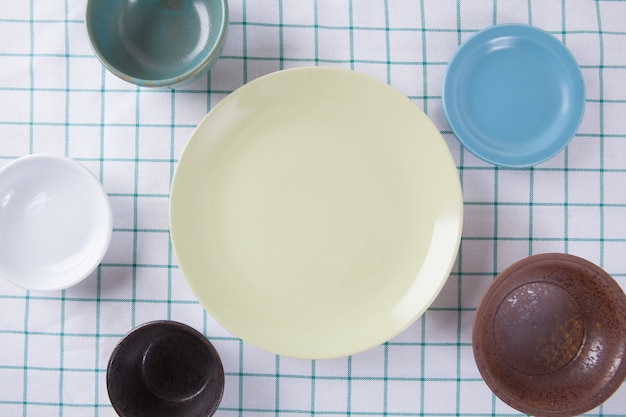 Bovenaanzicht van lege kleurrijke plaat op doek tafel met ruimte voor kopie.