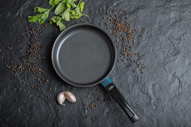 Bovenaanzicht van lege koekenpan op zwarte achtergrond met knoflook en paprika.