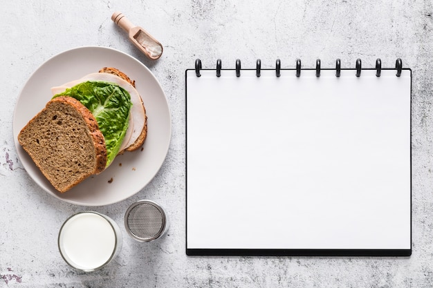 Bovenaanzicht van lege menu notebook met sandwich
