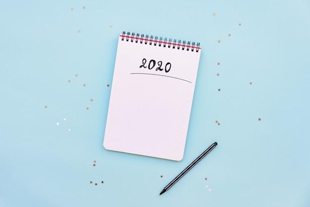 Bovenaanzicht van lege notebook klaar voor nieuwe 2020 jaar schaven of verlanglijstje