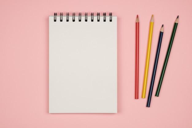 Bovenaanzicht van lege notitieboekpagina met kleurpotloden