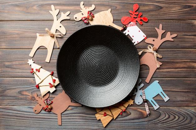 Bovenaanzicht van lege plaat en nieuwjaar decoraties op houten achtergrond. nieuwjaar serveert voor feestelijk diner. rendieren en kerstboom. vakantie familiediner