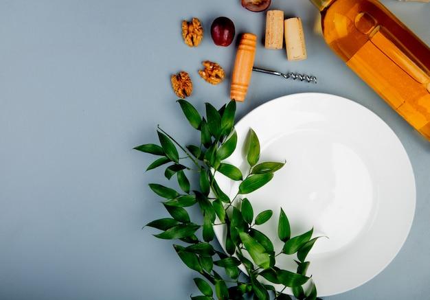 Bovenaanzicht van lege plaat met fles witte wijn walnoten kurkentrekker en bladeren op witte achtergrond met kopie ruimte