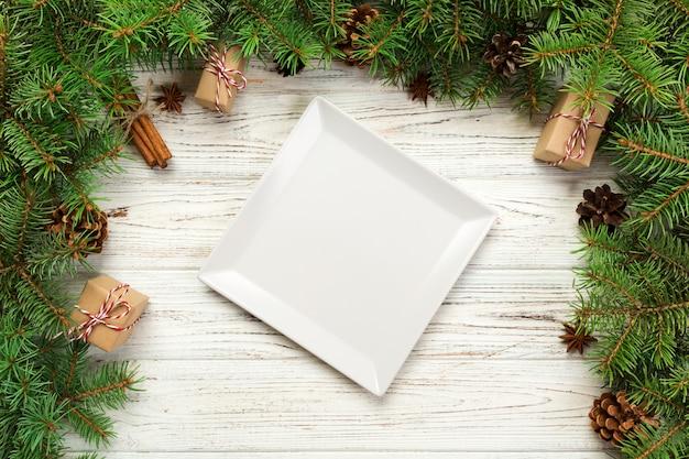 Bovenaanzicht van lege plaat op houten kerst tafel
