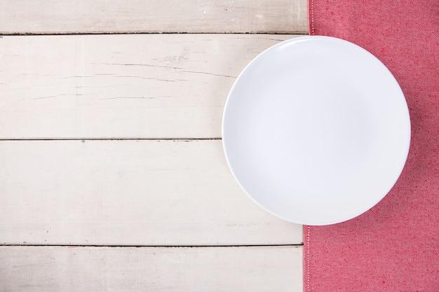 Bovenaanzicht van lege witte plaat op rode tafelkleed en witte houten tafel met ruimte voor kopie.