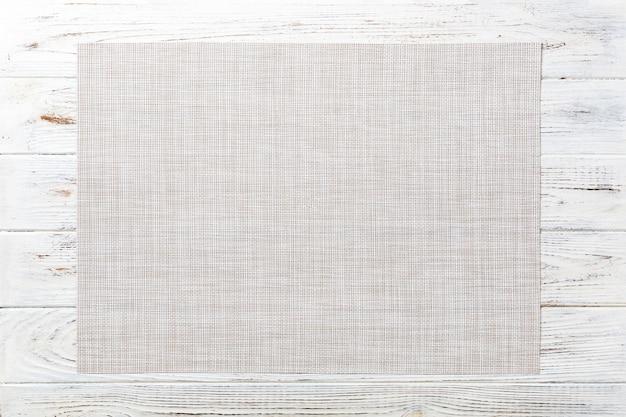 Bovenaanzicht van lege witte tafellaken op houten tafel