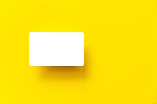 Bovenaanzicht van lege witte visitekaartje met schaduw op de achtergrond geel papier.