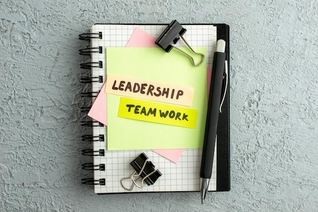 Bovenaanzicht van leiderschapsteamwerk op gekleurde enveloppen op spiraalvormig notitieboekje en boek op grijze zandachtergrond