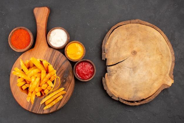 Bovenaanzicht van lekkere frietjes met sauzen op donker