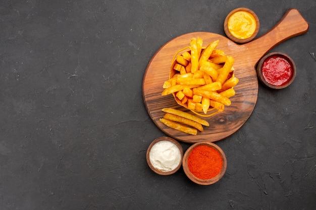 Bovenaanzicht van lekkere frietjes met sauzen op zwart