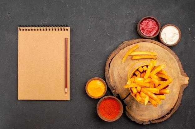 Bovenaanzicht van lekkere frietjes met sauzen op zwarte tafel