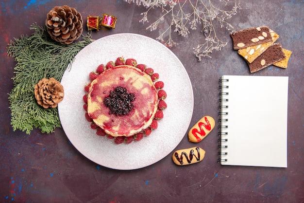 Bovenaanzicht van lekkere fruitige pannenkoeken met gelei en aardbeien op dark