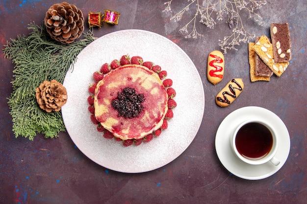 Bovenaanzicht van lekkere fruitige pannenkoeken met kopje thee op dark