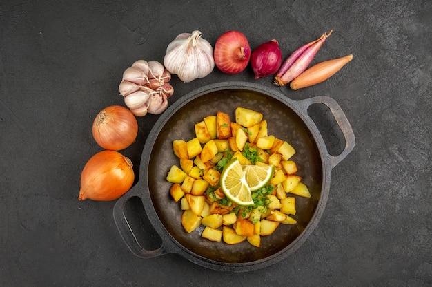 Bovenaanzicht van lekkere gebakken aardappelen in pan met citroen en knoflook rond op het donkere oppervlak