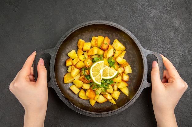 Bovenaanzicht van lekkere gebakken aardappelen in pan met schijfjes citroen op donkere ondergrond