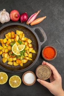 Bovenaanzicht van lekkere gebakken aardappelen in pan met verschillende kruiden op het donkere oppervlak