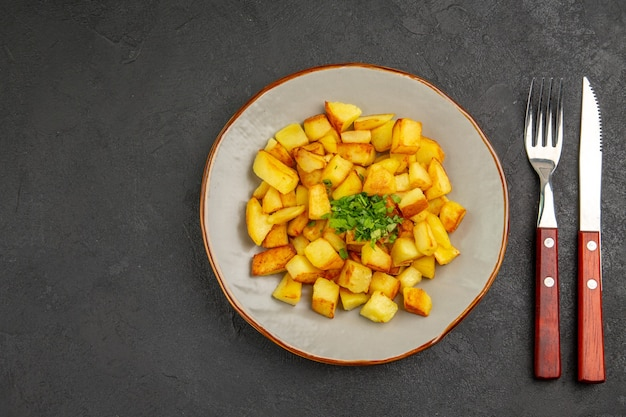 Bovenaanzicht van lekkere gebakken aardappelen in plaat met groenen op het donkere oppervlak