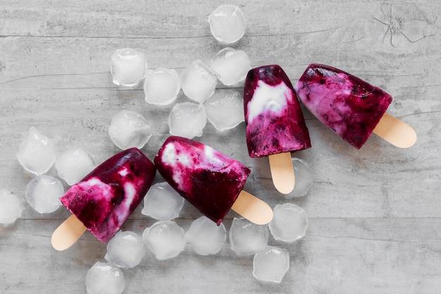 Bovenaanzicht van lekkere ijslollys met fruit en ijs