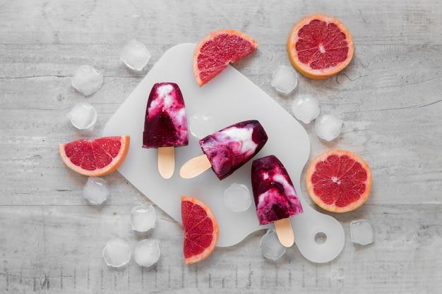 Bovenaanzicht van lekkere ijslollys met ijs en rode grapefruit