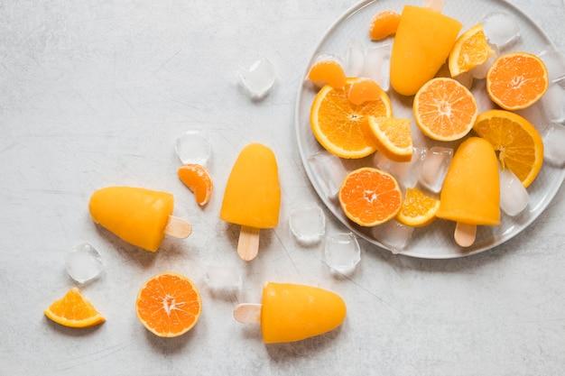 Bovenaanzicht van lekkere ijslollys op plaat met ijs en sinaasappel