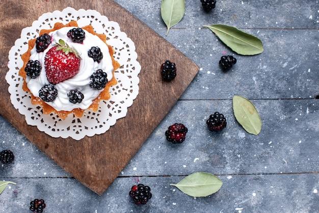 Bovenaanzicht van lekkere kleine cake met room en bessen op licht
