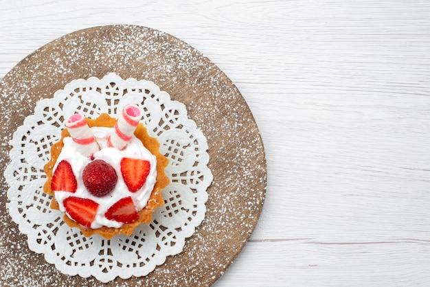 Bovenaanzicht van lekkere kleine cake met room en gesneden aardbeien op wit