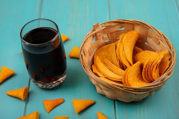 Bovenaanzicht van lekkere knapperige aardappelchips op een emmer met een glas cola op een blauwe houten tafel