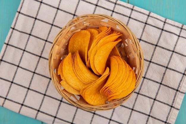 Bovenaanzicht van lekkere knapperige chips op een emmer op een gecontroleerde doek