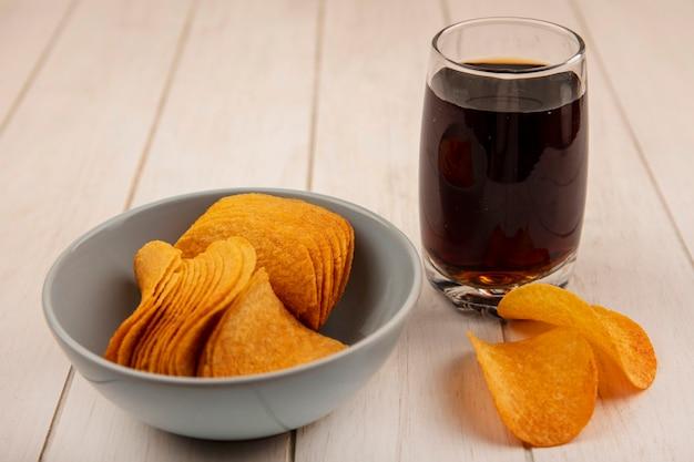 Bovenaanzicht van lekkere knapperige chips op een kom met een glas cola op een beige houten tafel