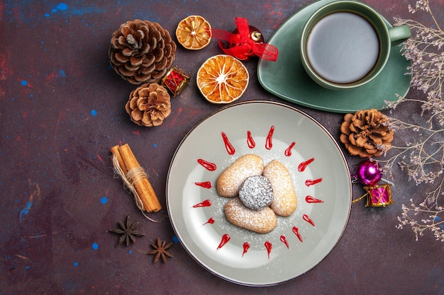 Bovenaanzicht van lekkere koekjes met kopje thee op zwart
