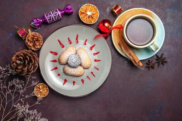 Bovenaanzicht van lekkere koekjes met rode glazuur en kopje thee op zwart