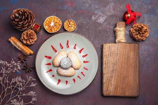 Bovenaanzicht van lekkere koekjes met rode glazuur in plaat op zwart