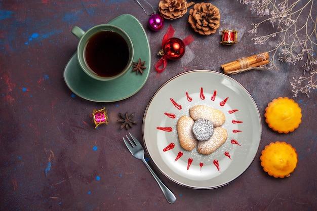 Bovenaanzicht van lekkere koekjes met suikerpoeder en kopje thee op donker
