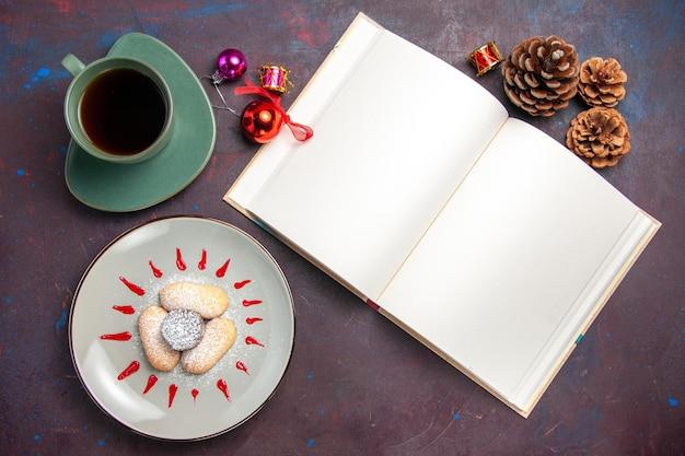 Bovenaanzicht van lekkere koekjes met suikerpoeder en kopje thee op zwart